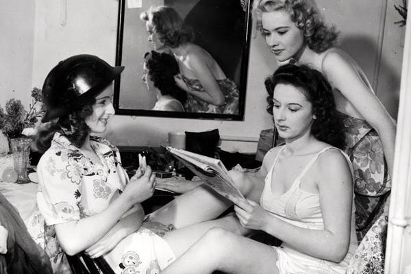 A time of hectic gaiety and abandon: at the height of the Blitz, dancers relax backstage at the Windmill theatre. Its famous slogan, 'We Never Closed', was popularly rendered as 'We Never Clothed'