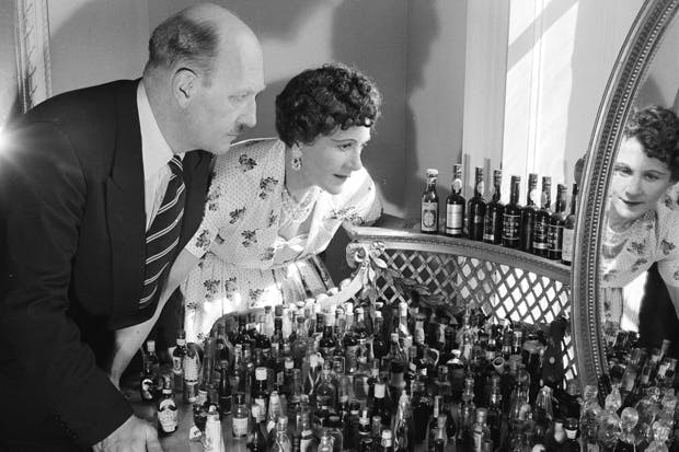 Fanny and Johnnie Cradock contemplate their collection of miniatures, 1956