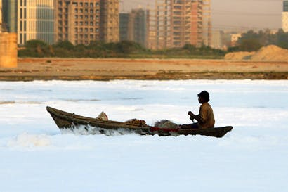 A dreadful warning: a fisherman paddles through a tide of toxic waste on the Yamuna river, against a backdrop of smog and high-rise construction