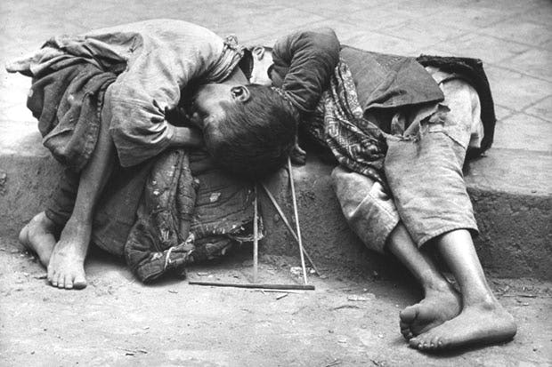 Two small children dying together in the gutter in the Chinese famine of 1946