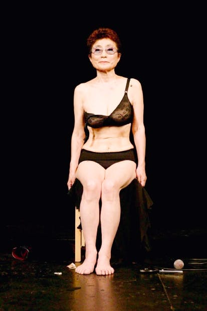Yoko Ono performing 'Cut Piece', where her outfit is cut down to her underwear by predatory snipping scissors