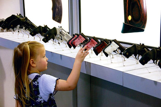 Fatal attraction: a four-year-old picks her favourite handgun at the NRA's annual meeting in Milwaukee, 2006