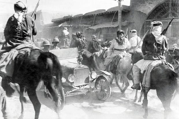 British officers in a modern motor car drive against the current of horsemen of the Arab army entering Damascus on 1 October 1918. Anglo-Arab policies were equally at cross purposes following the fall of the city