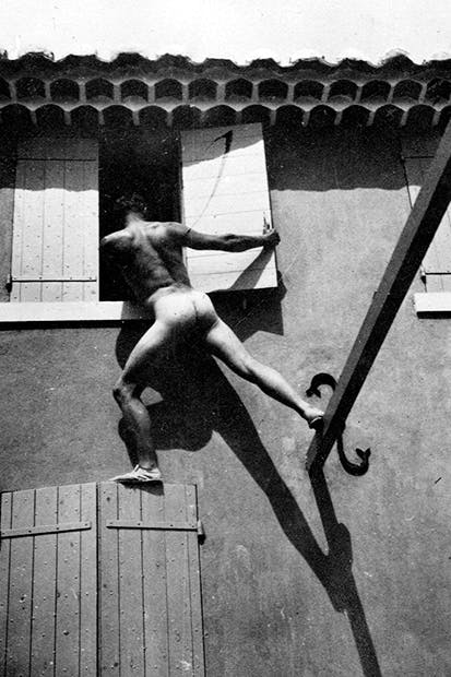 Bunny Garnett climbing into a window at La Bergère, Cassis, in the 1920s