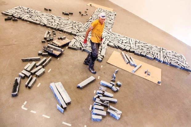 Richard Long installing the large slate cross, Time and Space (2015), at the Arnolfini