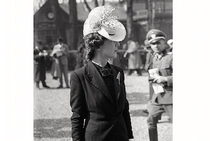 A stylish Parisienne catches the eye of a German officer at the Auteuil races, March 1941