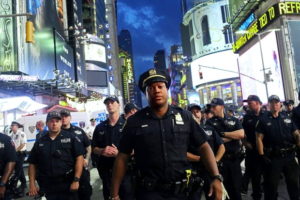 Police watch activists protest in Times Square in response to the recent fatal shootings (Photo: Getty)