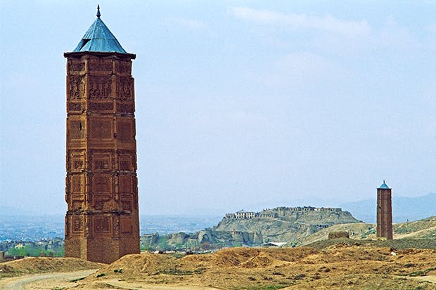 The two victory towers at Ghazna, Afghanistan, with the citadel in the background. To the left are the remains of the tower commissioned by Sultan Masud III ibn Ibrahim (r. 1099–1115). The tower on the right was built on the orders of Bahram Shah (r. 1117–1157)