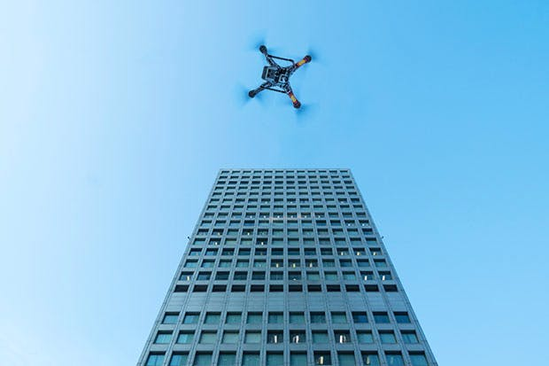 A drone hovers between two tower blocks