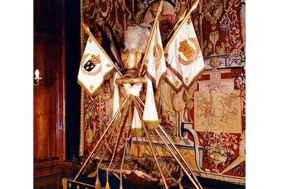 The cradle of Henri IV, made from a turtle shell edged with silver, is displayed under the royal flags of France and Navarre