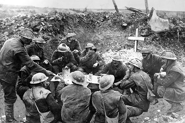 Soldiers on the Western Front celebrating Christmas Day in a shell hole partly occupied by the grave of a comrade