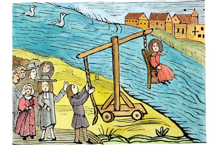 A woman on a ducking-stool, accused of witchcraft. Drowning would have proved her innocence