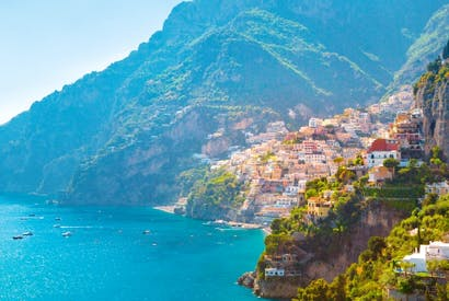 Positano's sun-bleached terracotta houses are set against rolling hills and an azure sea