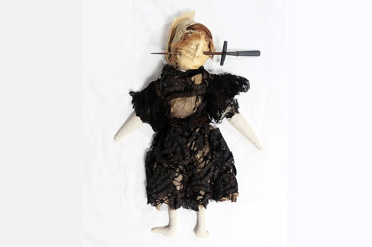 Stuffed doll in Edwardian-style black dress with stiletto through face, south Devon, England , 1909–13