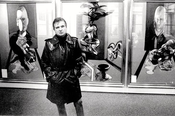 Francis Bacon in front of his triptych at the Galerie Claude Bernard in the Rue des Beaux Arts, Paris in 1977