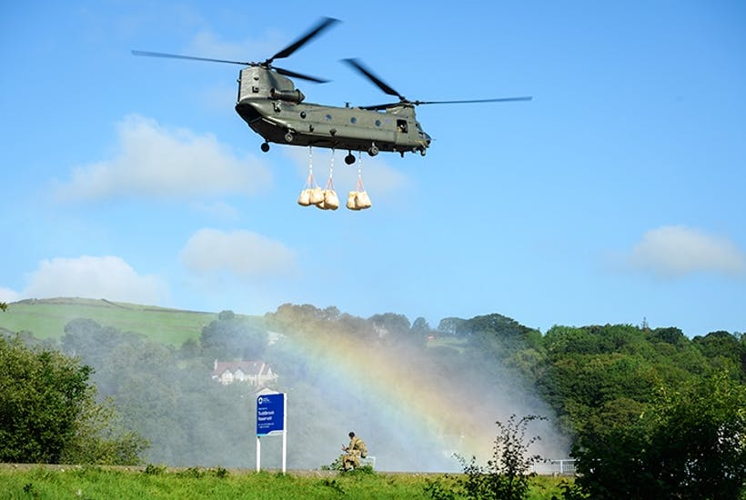 A Chinook helicopter prepares to drop sandbags onto the dam wall at the Toddbrook reservoir last week (Getty)